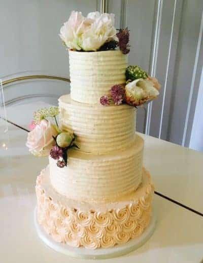 Bruidstraat afgesmeerd met botercreme en echte bloemen gemaakt door DS Patisserie.