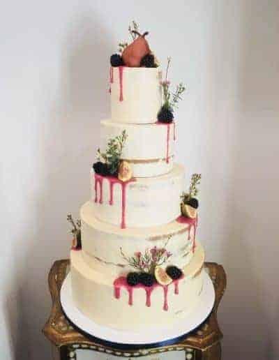 Semi-naked bruidstaart afgesmeerd met botercreme en gedecoreerd met fruit en vijgen gemaakt door DS Patisserie.