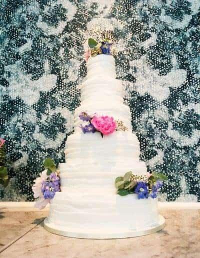 Bruidstaart bekleed met fondant door DS Patisserie, als decoratie echte bloemen.