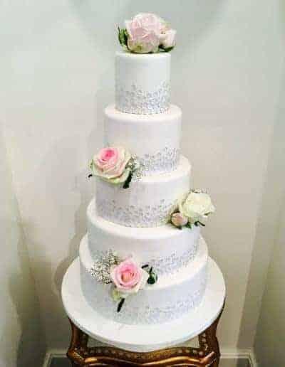 Bruidstaart bekleed met fondant en pailletten door DS Patisserie, als decoratie echte bloemen.