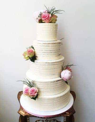 Bruidstaart afgemeerd met een botercreme gedecoreerd met echte bloemen gemaakt door DS Patisserie.