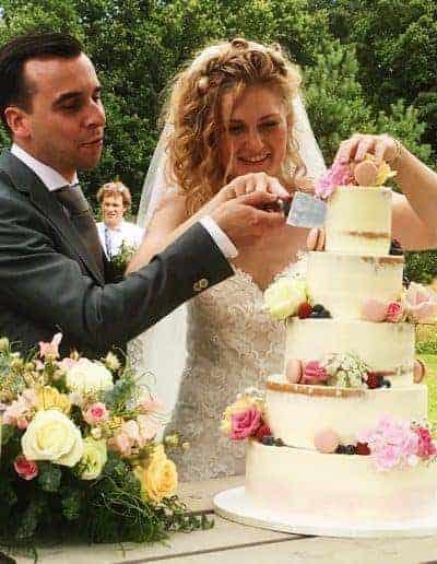Bruidstaart semi naked afgemeerd met een botercreme gedecoreerd met echte bloemen, fruit en macarons gemaakt door DS Patisserie.