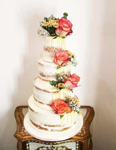 Bruidstaart met echte bloemen semi naked afgesmeerd met drip door DS Patisserie in Den Haag.