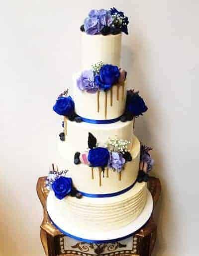 Bruidstaart met echte bloemen in blauw en paarse tinten afgesmeerd met een botercreme gemaakt door DS Patisserie.